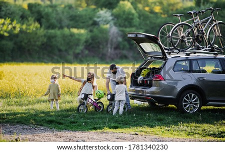 Family with two small children and face masks going on cycling trip in countryside. Royalty-Free Stock Photo #1781340230
