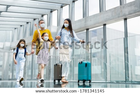 Family with two children going on holiday, wearing face masks at the airport. #1781341145
