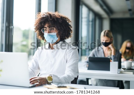 Portrait of young man with face mask back at work in office after lockdown. Royalty-Free Stock Photo #1781341268