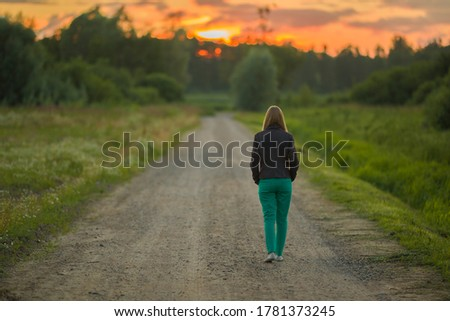 Young woman slowly walking on dirt road in dark summer evening. Orange sunset light in sky. Spending time alone in nature. Peaceful atmosphere. Back view. #1781373245