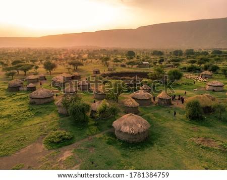 Aerial Drone Shot. Traditional Masai village at Sunset time near Arusha, Tanzania Royalty-Free Stock Photo #1781384759