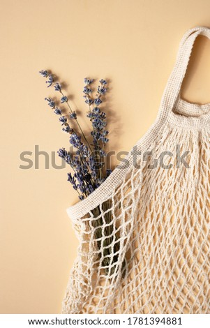 Natural mesh bag with a bouquet of lavender on a light background. Zero waste. Vertical picture.