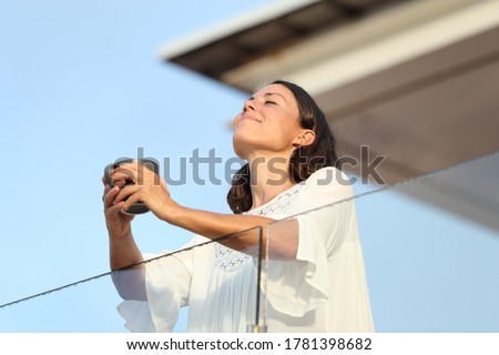Satisfied adult woman with coffee cup breathing fresh air on a hotel balcony at summer Royalty-Free Stock Photo #1781398682