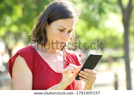 Serious adult woman using smart phone standing in a park a sunny day Royalty-Free Stock Photo #1781409197