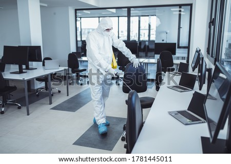 Office disinfection during COVID-19 pandemic. Man in protective suit and face mask spraying for disinfection in the office Royalty-Free Stock Photo #1781445011