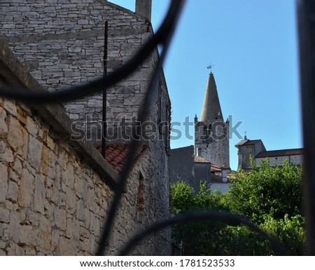 Bell Tower of Holy Spirit Church in Bale, Croatia pictured through fence