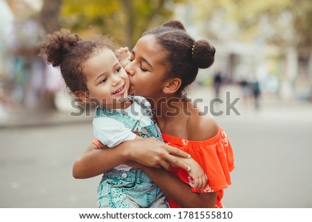 Outdoor picture of senior sister giving a kiss to her baby sister