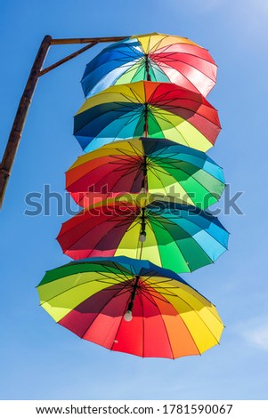 Street lamps decorated with colorful umbrellas hang on a pillar in street against the blue sky on a sunny day, Vietnam #1781590067