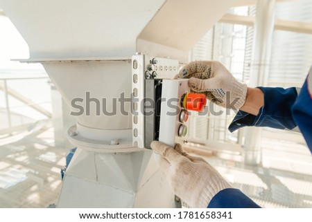 Red button. Panel with buttons. Panel mounting with buttons. The man is screwing the panel with the buttons with a screwdriver. Red and green buttons. Start and stop. #1781658341