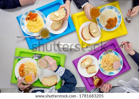 Children are having lunch in the school cafeteria. Top view of dishes on colored trays. Royalty-Free Stock Photo #1781683205