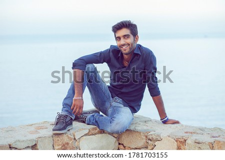 Man smiling looking to the side happy celebrating freedom while sitting on a concrete wall bridge above the sea. Positive person, peace mind concept. Free happy guy enjoying sunset #1781703155