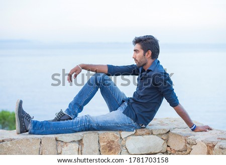Man thinking looking to blue sky while sitting on a concrete bridge above the sea taking deep breath enjoying freedom at sunset sea on background. Melancholic thoughtful person, peace mind concept. #1781703158