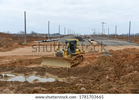 Bulldozer moves gravel during on road work at construction site. Dozer leveling stones for laying asphalt on a new freeway. Heavy machinery for earth-moving #1781703665