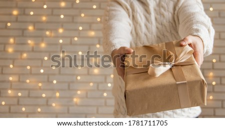 Christmas gift in man hands holiday wallpaper poster concept picture with white wall background and garland illumination lamps  Royalty-Free Stock Photo #1781711705