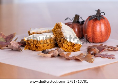 Pumpkin bars topped with cream cheese frosting surrounded with leaves, acorns, pumpkins and fall decor. Royalty-Free Stock Photo #1781713781