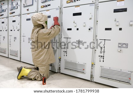 The electrician wear arc flash suit, electrical safety gloves and high voltage insulating boots to open power compartment door for rackout circuit breaker of medium voltage switchgear Royalty-Free Stock Photo #1781799938