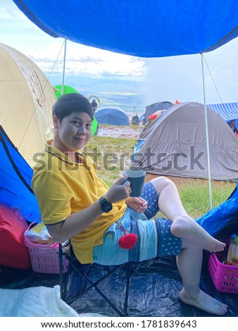 Young women drinking coffee in the background, landscape, tent field in the mountains among nature In the tropical forest in Thailand, color vintage pictures