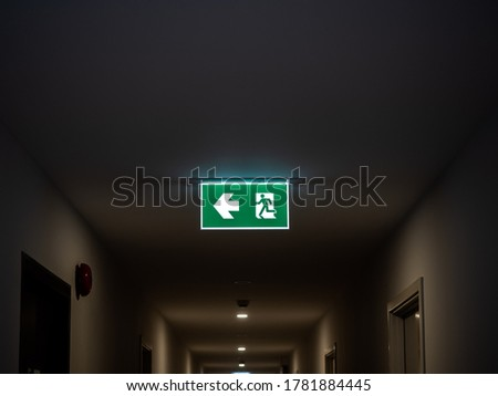 Fire exit. Illuminated green emergency exit sign hanging on ceiling in modern building in the dark in apartment.