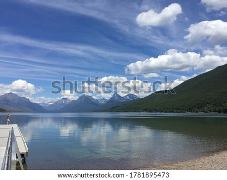 Tourist in a hat standing on a lake dock and taking photo of mountains and lake. Bright sunny calm day with blue sky and  white clouds reflected in transparent water of a mountain lake with pebbles