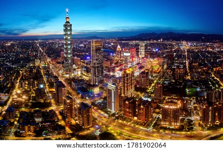 Aerial panorama of Downtown Taipei at dusk, the vibrant capital city of Taiwan, with 101 Tower standing out amid skyscrapers in Xinyi Commercial District & city lights dazzling under blue twilight sky