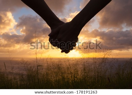Romantic couple holding hands and watching a beautiful sunset Royalty-Free Stock Photo #178191263