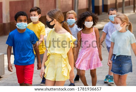 School children in protective medical masks walk along the street of a summer city #1781936657