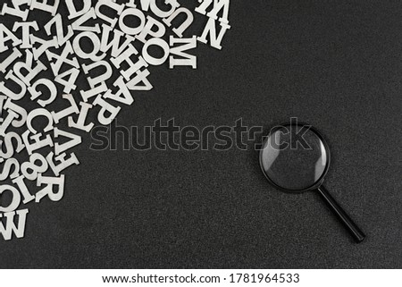 English alphabet letters and magnifying glass on black background. Search for words and information concept.