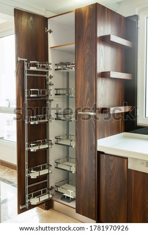 Modern kitchen, opened wooden drawers with accessories inside, solution for kitchen storage, minimalist interior design Royalty-Free Stock Photo #1781970926