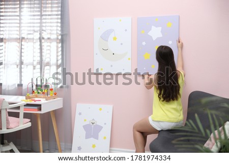 Decorator hanging picture on pink wall. Children's room interior design
