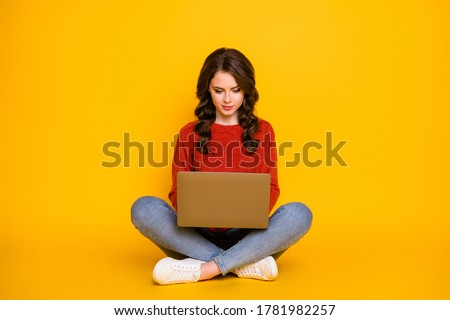 Full body photo of attractive curly lady good mood sitting floor working with computer stay home remote worker wear red knitted sweater blue jeans isolated bright yellow color background