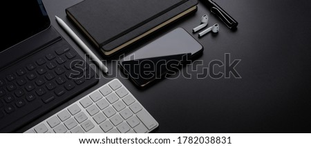 Cropped shot of digital devices with smartphone, tablet, keyboard, stationery, accessories and copy space on dark table Royalty-Free Stock Photo #1782038831