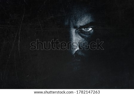 Dark man portrait with scary evil eye. Spooky male face hiding in shadow, creepy frightening expression Royalty-Free Stock Photo #1782147263