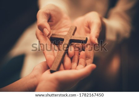 Woman's hand with cross .Concept of hope, faith, christianity, religion, church online. Royalty-Free Stock Photo #1782167450