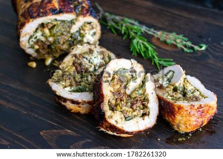 Mediterranean Stuffed Pork Tenderloin: Roasted pork stuffed with spinach, pesto, and goat cheese on a dark wood background #1782261320
