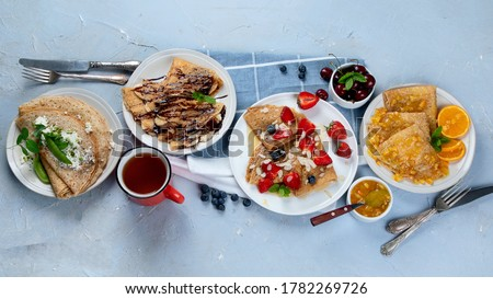 Variety of fresh crepes with jam, fruits and berries on grey background. Homemade delicious crepes. Top view, copy space. Royalty-Free Stock Photo #1782269726