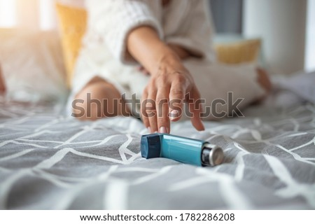 Asmathic girl catching inhaler having an asthma attack. Young woman having asthma attack. She is holding inhaler. Asthmatic woman using an asthma inhaler during asthma attacks  Royalty-Free Stock Photo #1782286208