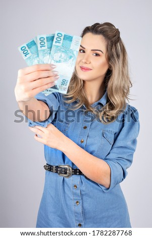 woman with Brazilian real money to give away one hundred reais Royalty-Free Stock Photo #1782287768