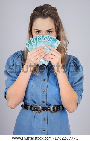woman with Brazilian real money to give away one hundred reais Royalty-Free Stock Photo #1782287771