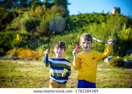 Two active preschool boy playing badminton in outdoor court in summer. Kids play tennis. School sports for children. Racquet and shuttlecock sport for child athlete. Friends happy together warm field. #1782384389