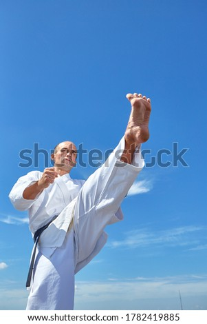 A sportsman in karategi trains a kick against a blue sky with clouds Royalty-Free Stock Photo #1782419885