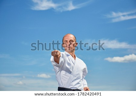 In karategi, the athlete performs a punch against the blue sky Royalty-Free Stock Photo #1782420491