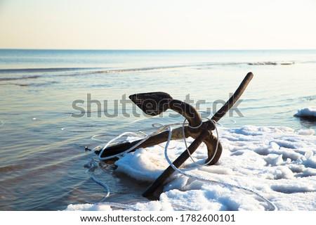 An patinous anchor alongside frozen seashore in winter