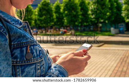 Taking picture. Happy young girl with phone smile, typing texting and taking selfie in summer sunshine urban city. Pretty female taking fun self portrait photo. Vanity, social network concept.