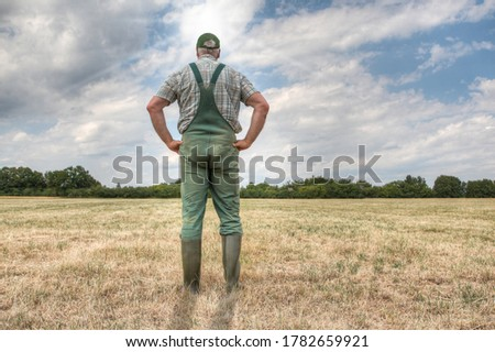 A farmer stands on his parched meadow and hopes for rain while the sun shines mercilessly on his farmland. Rising temperatures and too little rain the arable land in Germany is dry like never before. Royalty-Free Stock Photo #1782659921