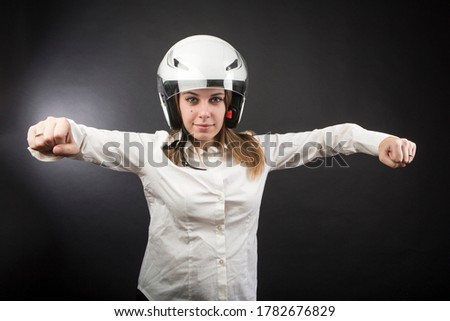 blonde girl with motorcycle helmet pretends to speed up a motorcycle, isolated on black background Royalty-Free Stock Photo #1782676829