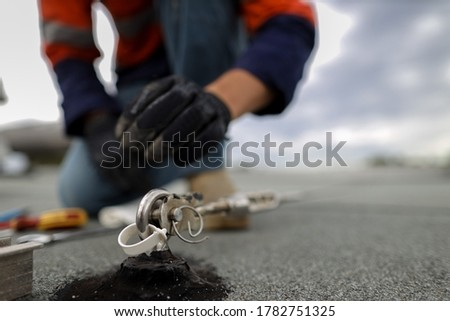Safety workplace industrial rope access working at heights fall arrest, abseiling stainless 16 MM dimension certifies anchor point installed on concrete rooftop defocused safety auditor background