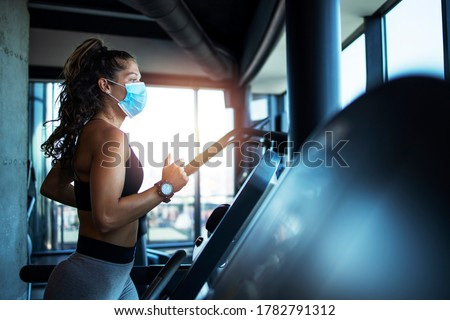 Sportswoman training on treadmill in gym and wearing face mask to protect herself against coronavirus during global pandemic of covid-19 virus. #1782791312