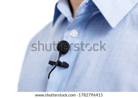sound recording and broadcasting concept - close up of small lavalier clip-on microphone on male shirt