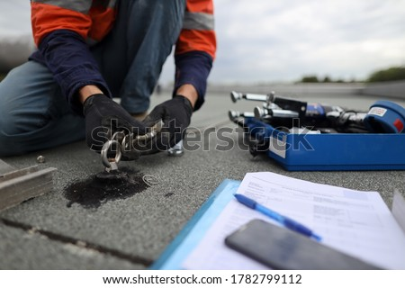 Safety workplace trained safety auditor  inspecting industrial working at heights lifeline fall arrest, abseiling stainless 16 MM dimension certifies anchor point installed on concrete rooftop