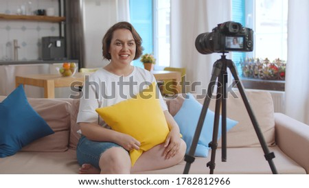 Female obese blogger recording video for overweight people sitting on couch at home. Plus size pretty lady filming video for internet blog about body positive and healthy lifestyle